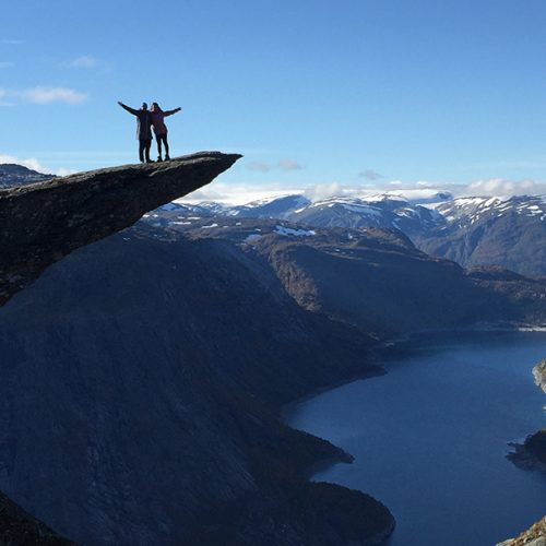 Two people standing on top of Trolltunga, Norway