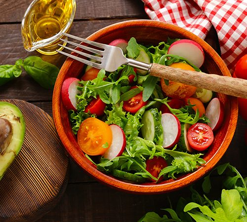 Big bowl of salad with tomatoes, olive oil and avocado