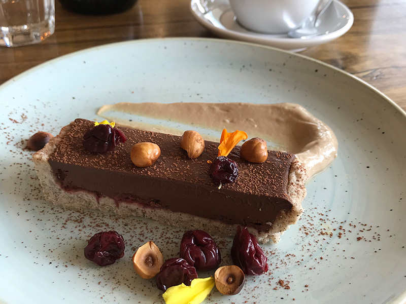Vegan chocolate tart with macadamias and cherries and coffee cream on a plate. Photo taken at Sister of Soul St Kilda