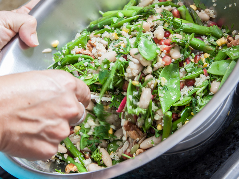 Pomegranate and quinoa salad being tossed in a stainless steel bowl
