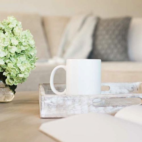 mug on tray next to flowers on coffee table in front of lounge