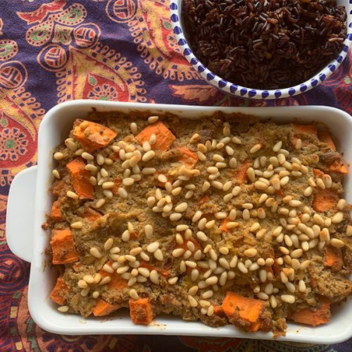 Large dish of sweet potato and tofu vegan bobotie with a side of black rice