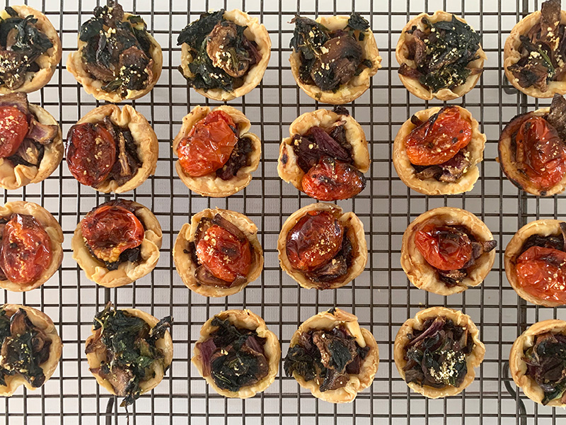 Rows of cooked cherry tomato tarts and mushroom and spinach tarts, cooling on a wire rack.