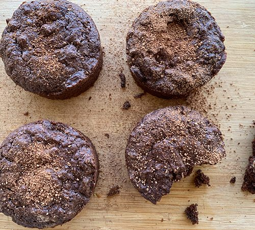 Four chocolate muffins on a timber chopping board
