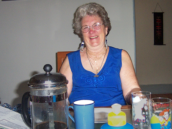 Overweight woman smiling, sitting at dinner table