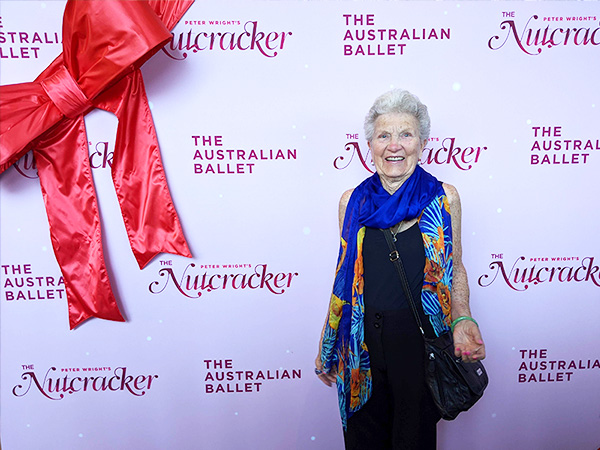 Older woman, smiling, standing in front of The Nutcracker media wall